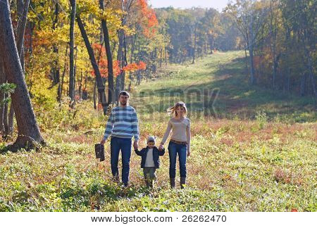 young family walking in the fall park