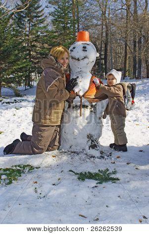 familia feliz de la madre con el niño haciendo el muñeco de nieve