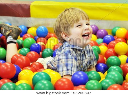 happy  kid playing with colored balls