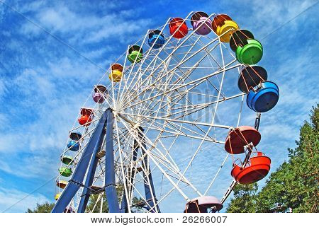 Brightly colored Ferris wheel against the blue sky