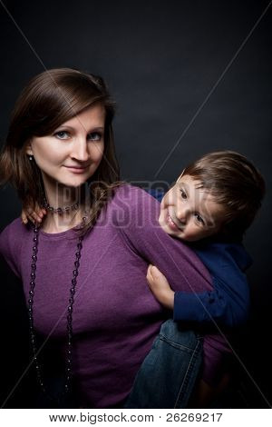 mother holding his son a piggyback ride