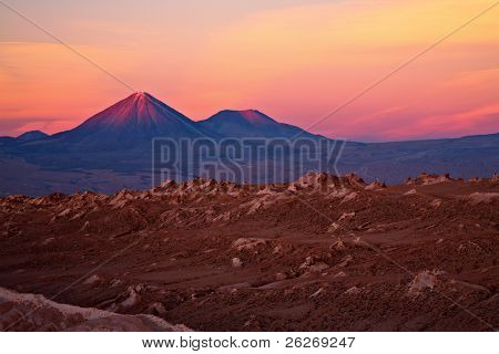 sunset over volcanoes Licancabur and Juriques and Valle de la Luna, Atacama desert, Chile