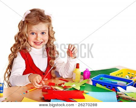 Little girl with scissors and glue in school.