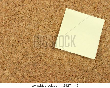 Blank yellow note paper stick on a corkboard