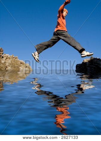 Child Jumping Rocks On Beach Vacation
