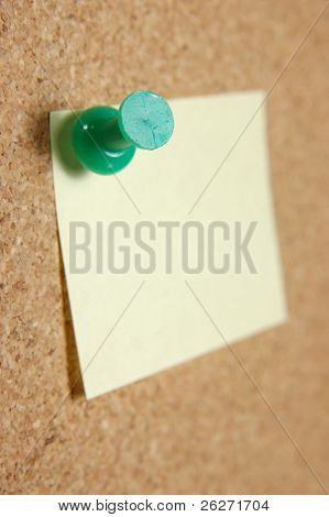 Close up of green pushpin with post-it note on corkboard