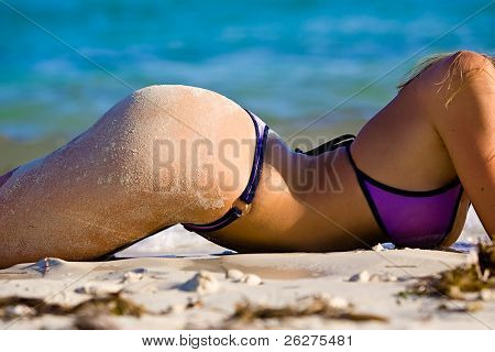 Blond model laying on beach wearing a thong bikini