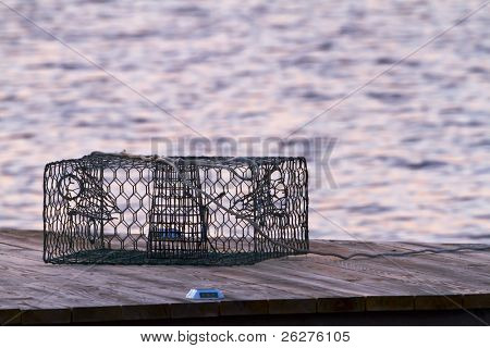 A crab pot sits on a pier in the early morning light