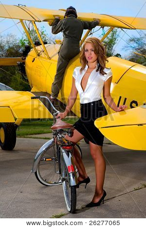 Blonde model standing near a WWI biplane