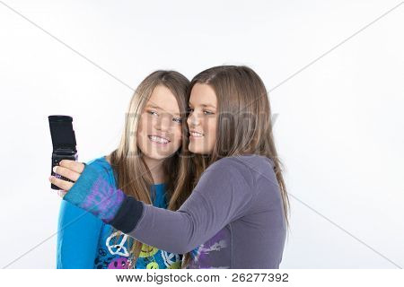 Twin sisters using cell phones in a studio environment on a white background