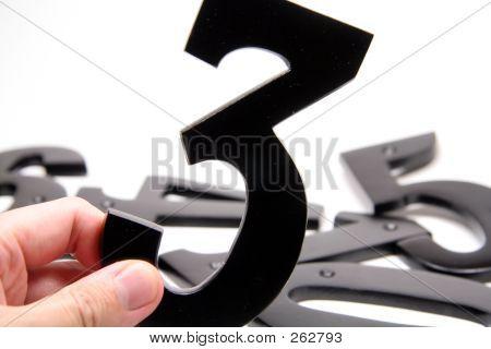 Mão segurando o número 3