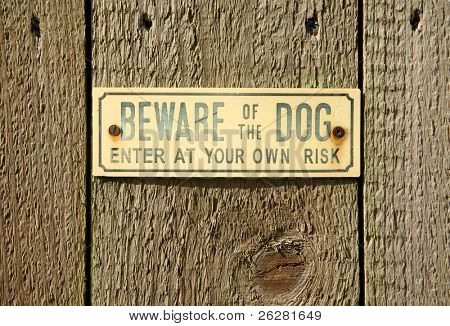 A beware of the dog sign on a wooden fence.