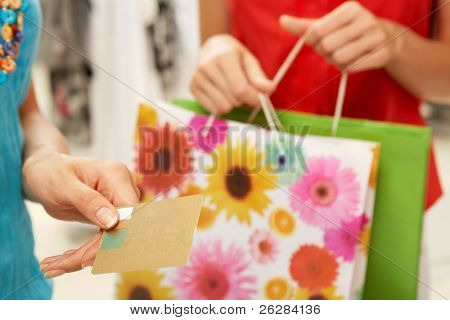 Close-up of female hand holding credit card during shopping