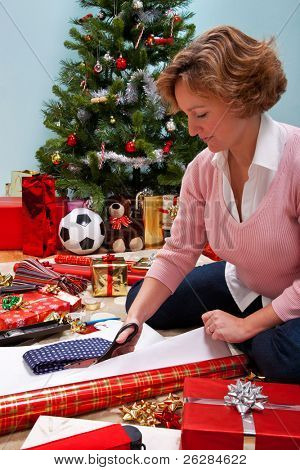 Photo of a woman sat on a rug at home wrapping her Christmas presents, Christmas tree in the background and gifts and paper around her. The teddy is generic and is not a brand bear.
