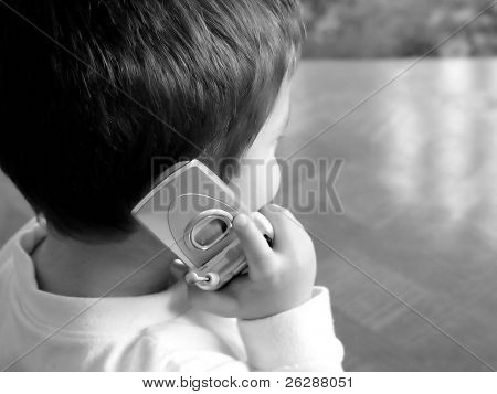 Little boy talking on a cellular phone in black and white