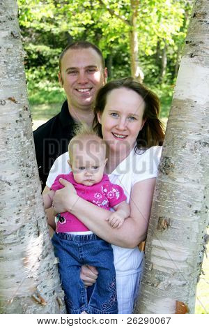 Young family together in trees on spring day