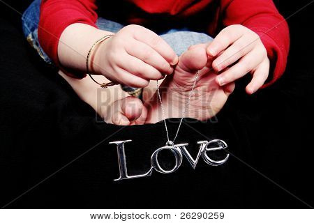 LOVE - Little baby with word LOVE hanging on her toes with black background