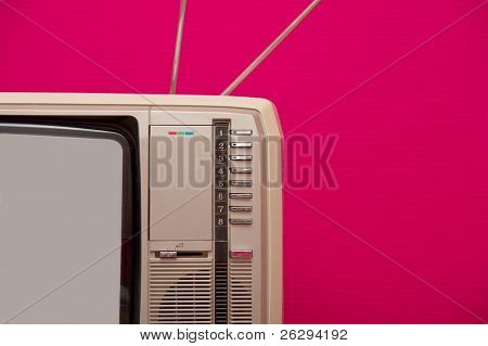 Detail of an old vintage tv set against pink wall