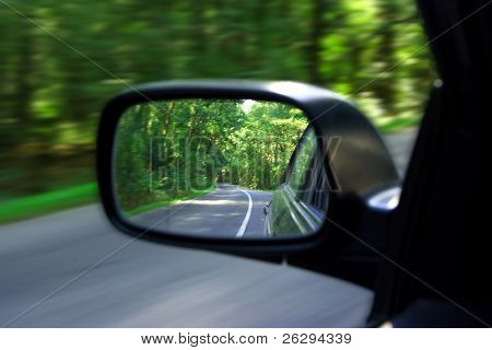 Landscape in the sideview mirror of a speeding car
