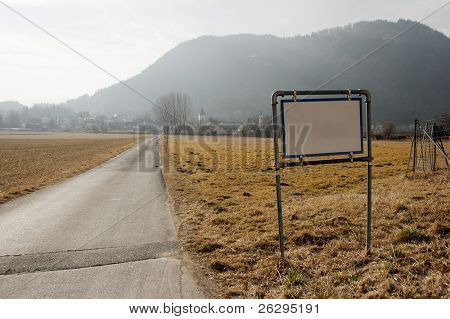 Narrow rural road with blank signboard