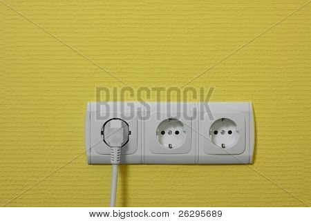 Electric outlets on the wall with a plug attached