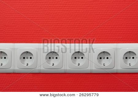 Endless row of electric outlets on red wall