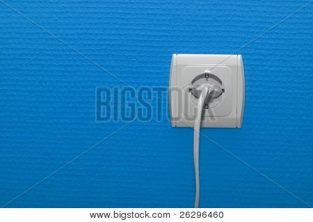 Electric outlet on blue wall