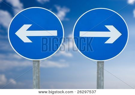 Contradicting directional signs against blue sky