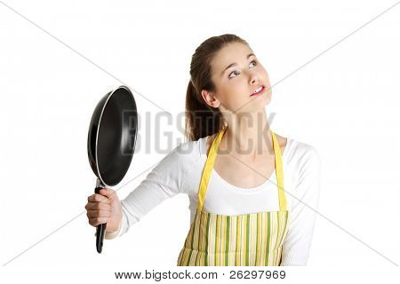 Front view portrait of a young upset caucasian female teen dressed in apron, holding a frying pan net to her, looking at the right top corner, on white.