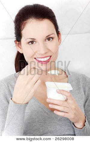 Front view portrait of a beautiful young smiling woman holding a small spoon of yogurt next to her lips.