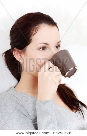 Site view portrait of a young beautiful woman drinking a cup of coffee / tea.