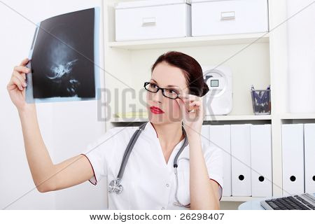 Pretty caucasian female doctor looking at x-ray.