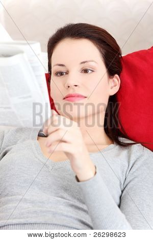 Front view portrait of a young beautiful smiling woman lying on a sofa, resting her head on a red pillow and reading a neswspaper.
