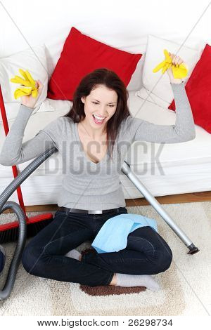 Front view of a full lengh young woman cleaning up at home, sitting on the floor next to the vacuum cleaner and a broom.