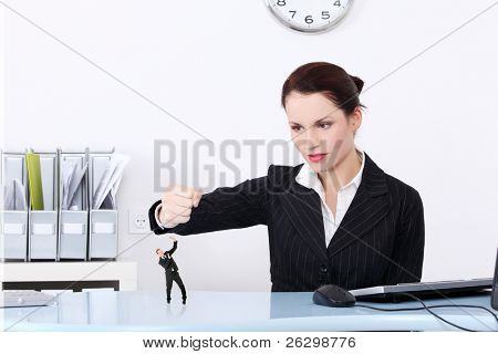 Bisnesswoman holding her fist bayond a miniature of a worker she wants to destroy.
