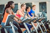 brunette beautiful woman smiling while cycling on a modern fitness bicycle during group spinning cla poster
