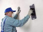 stock photo of spreader  - Plasterer smoothing out wall with trowel - JPG