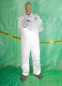 stock photo of decontamination  - Man in Hazmat clothing in temporary green plastic decontamination chamber wearing a gas mask and carrying toxic chemical that is exuding gaseous vapor - JPG