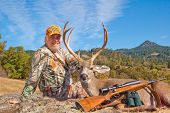 foto of black tail deer  - Successful hunter with his game - JPG