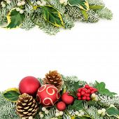 Christmas festive background border with red bauble decorations, holly berries, snow covered spruce  poster
