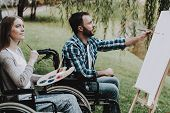 Disabled Young Man On Wheelchairs Drawing In Park. Disabled Young Man. Smiling Woman. Relaxing In Su poster
