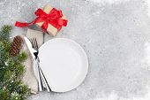 Christmas table setting with gift box and fir tree branch covered by snow on stone background. Empty poster