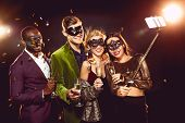 Glamorous Multicultural Friends In Carnival Masks Taking Selfie On Smartphone poster