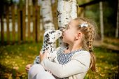 Cute Girl Kissing Her Puppy, Doggy On The Wood Fence Background.happy Girl With A Dog Licking Her Fa poster