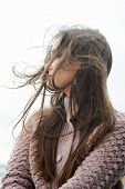 Beautiful smiling brunette woman profile portrait, chic long hair fluttering in the wind, soft focus poster