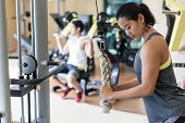 Side view of a determined young woman exercising cable rope triceps extension during upper-body work poster