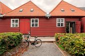 Traditional Wooden House In Historical Area Of Copenhagen, Denmark. Bicycle Parked Past Old Red Hous poster