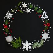 Abstract Christmas wreath garland with winter flora and bauble decorations on black background. Top  poster