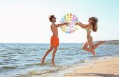 Happy Young Couple In Beachwear Jumping With Inflatable Ball On Seashore poster