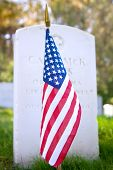 American flag in front of a gravestone in a military cemetery